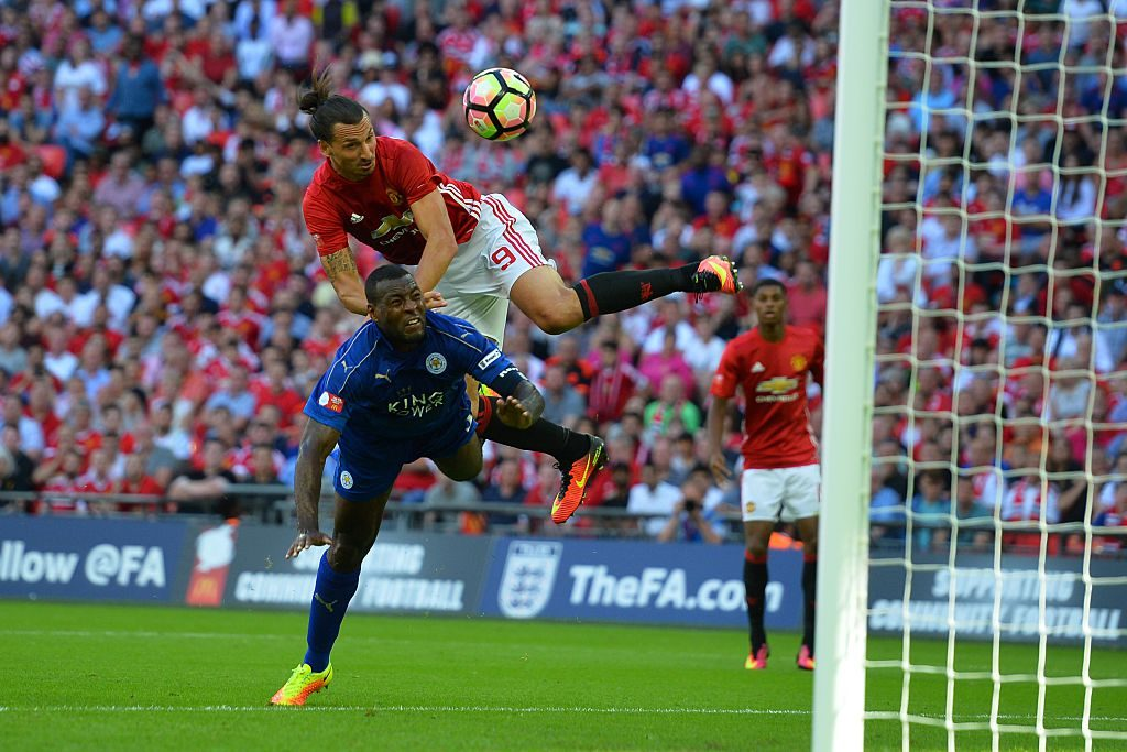 Manchester United's Swedish striker Zlatan Ibrahimovic (up) beats Leicester City's English defender Wes Morgan (down) to head in their second goal during the FA Community Shield football match between Manchester United and Leicester City at Wembley Stadium in London on August 7, 2016. / AFP / GLYN KIRK / NOT FOR MARKETING OR ADVERTISING USE / RESTRICTED TO EDITORIAL USE (Photo credit should read GLYN KIRK/AFP/Getty Images)