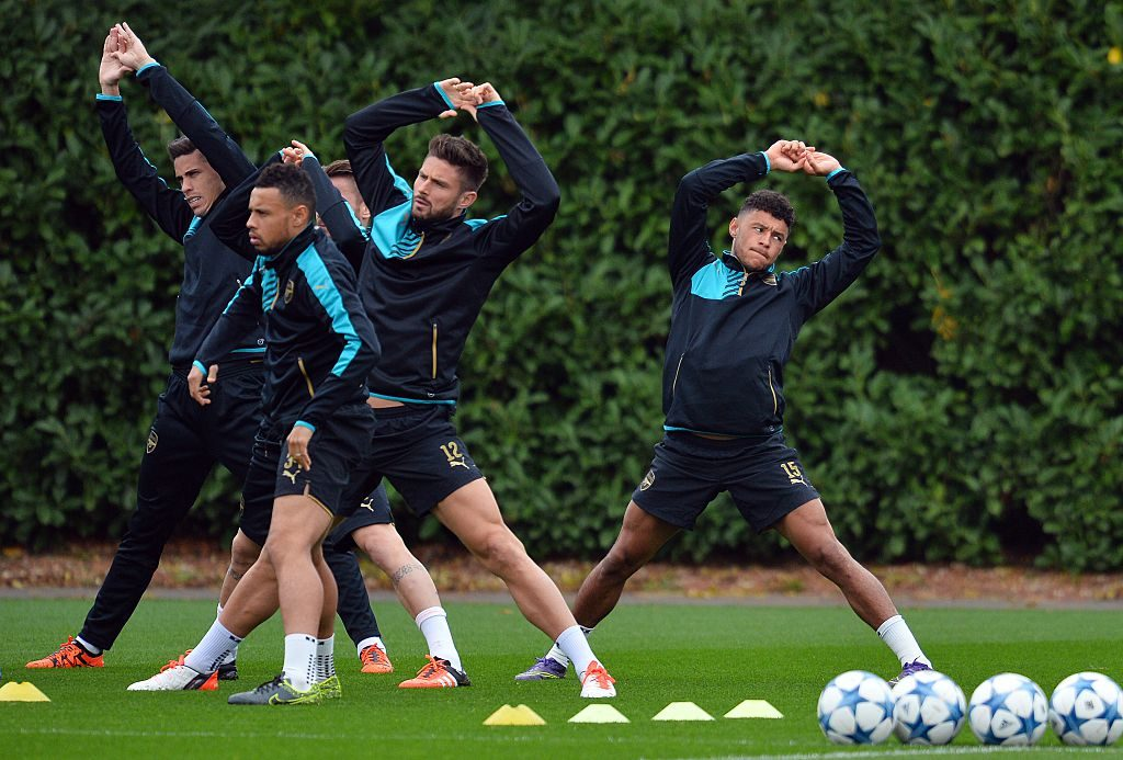 Arsenal's English striker Alex Oxlade-Chamberlain (R) stretches during a training session at their London Colney training ground in Hertfordshire, north of London, on October 19, 2015 on the eve of their UEFA Champions League group stage F football match against Bayern Munich.  AFP PHOTO / GLYN KIRK        (Photo credit should read GLYN KIRK/AFP/Getty Images)